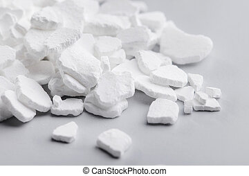 Calcium chloride (CaCl2) flakes. Common applications include brine for refrigeration plants, ice and dust control on roads, and desiccation.