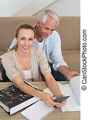 calculador, pareja, sofá, su, sonriente, cuentas
