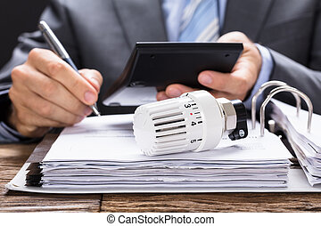 Calculating Energy Costs - Midsection of businessman...