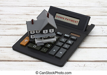 Calculating your down payment, A gray model house on a calculator with words Down Payment over a distressed wood background