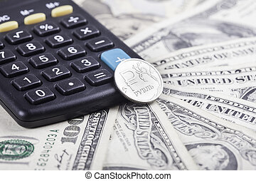 calculator and coin ruble on the background of dollars