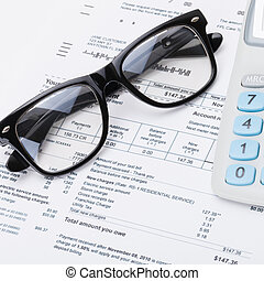 Calculator and glasses with utility bill under it - close up shot