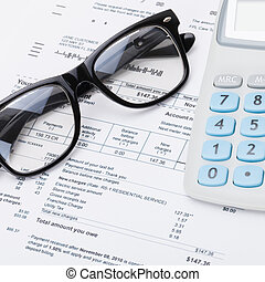 Calculator and glasses with utility bill under it - studio...