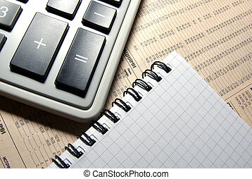 Calculator and notebook laying on financial newspaper.