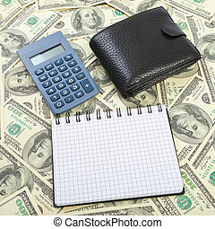 Calculator and notebook on a dollars