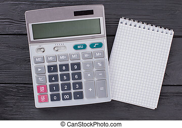 Calculator and notepad on dark wooden table.