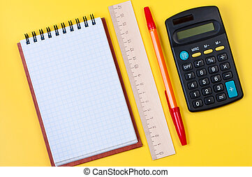 Calculator and notepad on yellow background top view.