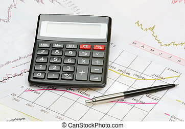 calculator and pen on a financial charts