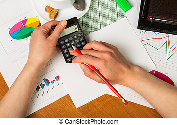 Calculator and pencil in female hands on background of desktop.