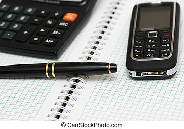 Calculator, ballpen and mobile phone on the notebook -...