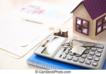 Calculator, House Model, Notebook, Key on Table