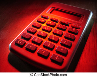 Calculator in Red - A calculator in red spotlight.