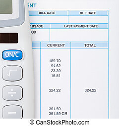 Calculator next to a bill - studio shot - 1 to 1 ratio