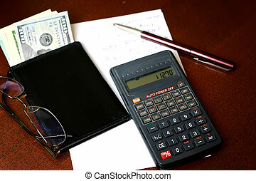 calculator on the table glasses money