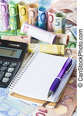 Calculator pen and notebook on the money
