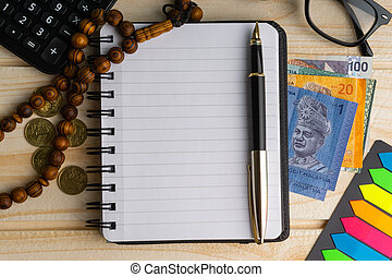 Calculator, rosary, coins, banknotes, book, spectacle and pen on wooden background.
