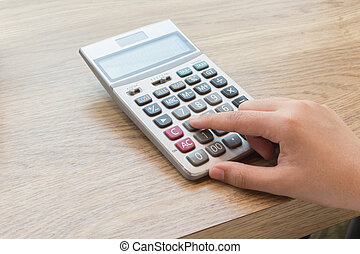 Calculator with hand on wood desk.