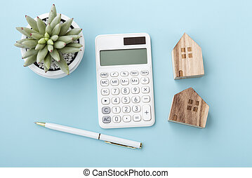 Calculator with house model, home loan or mortgage concept