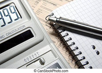 Calculator with numbers on display, pen and notebook laying on newspaper.