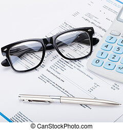 Calculator with pen, glasses and utility bill under it - close up shot