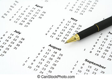 calendar and ballpoint pen - close-up of simple white yearly...
