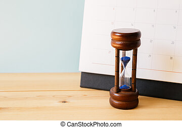 Calendar and hourglass on table, Business schedule and time concept