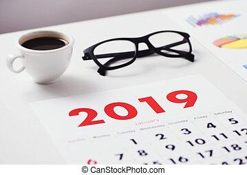 calendar of 2019, coffee, eyeglasses and charts - closeup of...