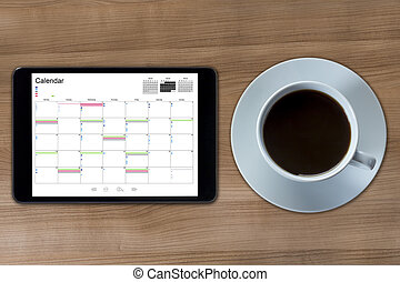 Calendar on a Tablet computer and cup of coffee
