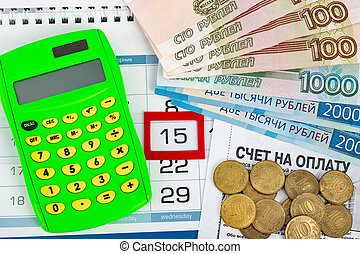 Calendar with a dedicated 15 number, calculator, Russian rubles banknotes and coins