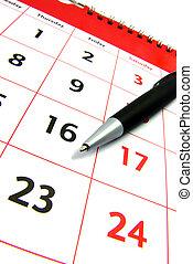 Calendar with a pen - Detail view of a calendar with a pen.