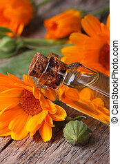 Calendula oil in a glass bottle closeup vertical