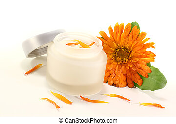 Calendula ointment with fresh marigold flowers, leaves and petals on a light background
