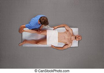 calf and knee massage - male therapist massaging muscular...