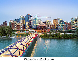 Calgary downtown with iluminated Peace Bridge, Alberta, Canada