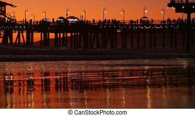 California summertime beach aesthetic, golden sunset. Vivid sky over pacific ocean waves. Santa Monica popular resort, Los Angeles CA USA. Famous pier against atmospheric moody evening sundown in LA.