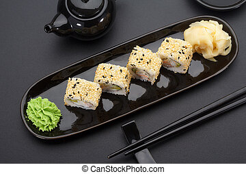 California sushi roll on a black plate