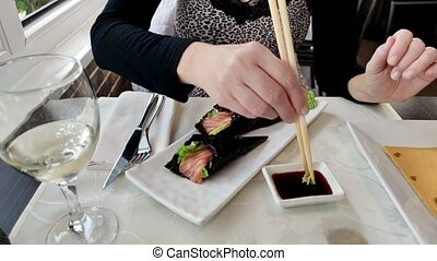 focus on California Temaki cone with shrimp tempura, rice, avocado and seaweed, in soy sauce bowl. Japanese fusion food, Asian cultures. Healthy food, light diet concept.