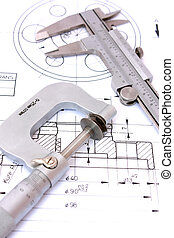 Caliper and Micrometer on blueprint vertical. Shallow depth of field.