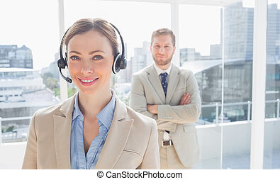 Call center agent standing with colleague behind her