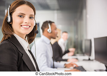 Attractive young woman in suit sitting at call center office with colleagues and working.