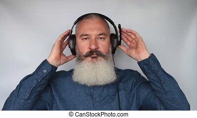 Call center employee puts headset on head, mature caucasian bearded man puts on his headphones, looks happy and thumbs up, grey background.