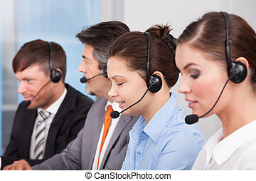 Call center operator sitting in row working at office