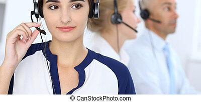 Call center operators at work. Focus at beautiful latin american woman in headset