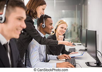 Side view of female manager assisting her staffs in a call center.