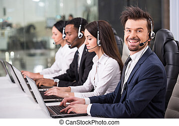 Call center - Side view of line of call centre employees are...