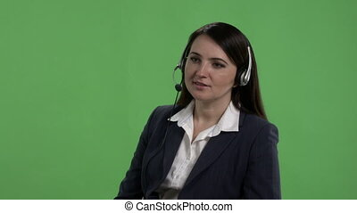 Call center worker with headset takes phone call against green screen
