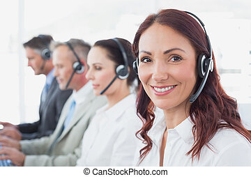 Call center workers wearing headsets and using computers