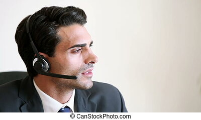 Call centre agent talking with a client while wearing his...