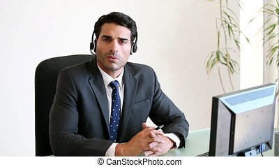 Call centre agent using a headset while sitting in his office