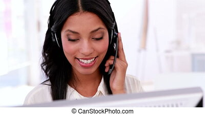 Call centre agent working and talking on headset in the...